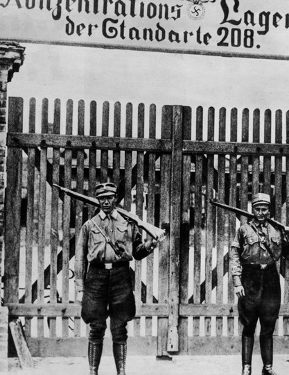 SA-bewakers voor het concentratiekamp van Oranienburg, 1933–34. In 1939 zaten 21.000 gedetineerden opgesloten in Konzentrationslager als Dachau, Sachsenhausen en Buchenwald. Koblenz, Bundesarchiv