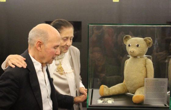 """Ondergedoken kind Norbert Vos-Obstfeld en zijn """"onderduikzus"""" Mona Verhage onthullen de teddybeer die Norbert door de oorlog hielp in de permanente tentoonstelling van Kazerne Dossin (03.10.2018)"""